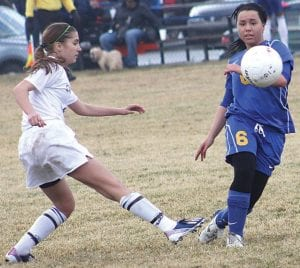 Carman-Ainsworth's Melody Bamford (8) boots the ball away from Kearsley on Monday at home to open the season.