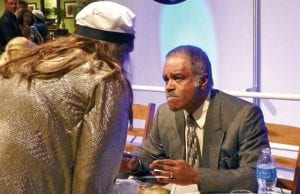 Ted Lange, aka Isaac from The Love Boat, autographs photos and chats with a fan.