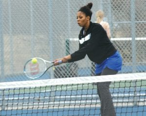 Carman-Ainsworth's Breanna Hudson connects on a backhand return.