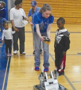 Top, young children got a chance to feed Frisbees to a complex robot used in competitions this year by the high school robotics team. Above, robotics team members were on hand to teach younger kids how to operate the controls of a robot.