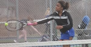 Carman-Ainsworth's Cionna Orr swats a forehand return that nearly got away from her.