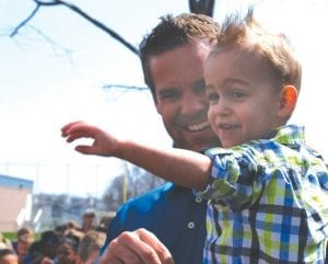 Easton Clark is held by his dad as he tries to pop a bubble.