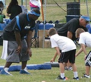 Detroit Lions' defensive lineman Andre Fluellen instructs athletes at the 2012 skills camp.