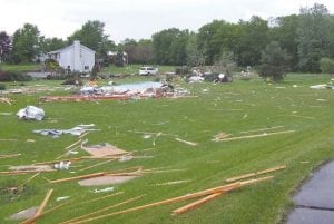 A wide view of the debris field behind the Mahaffy home, showing where the neighbor's business once stood.