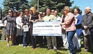 Above, GM Foundation officials presented checks totaling $83,800 to 16 Flint-area organizations.