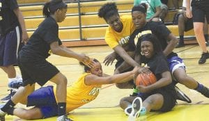 Former Carman-Ainsworth teammates Ashley Hall (gold jersey, on floor) and Montreca Mull (seated, with ball) scrap for a loose ball in the Bruin Club All-Star Classic last Thursday at Mott Community College.