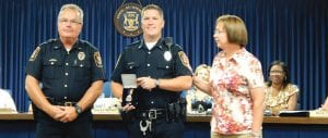 Officer Neal Donovan (center) receives the Medal for Meritorious Service from Police Chief George Sippert and Township Supervisor Karyn Miller.