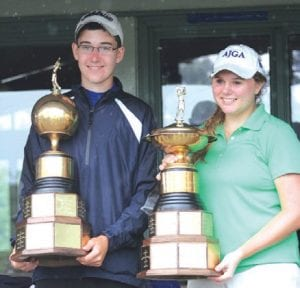 Ben Zyber and Kristen Wolfe display their championship trophies after the final day at Swartz Creek Golf Course.