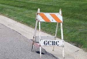 A road commission construction sawhorse alerts motorists of small hole in the street.