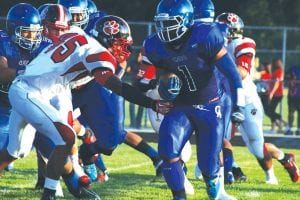 Carman-Ainsworth's Malik Seales (1) carries the ball against Grand Blanc in the season-opener.
