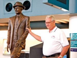 Joseph Rundell, a Clio sculptor, poses with his newly unveiled creation, a bronze statue of auto pioneer Walter P. Chrysler, now on permanent display at Bishop Airport.