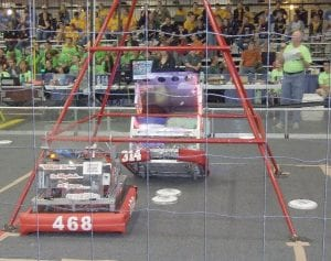 The colorful Carman-Ainsworth robot 314 (The Megatron Oracles (Big Mo) takes a high shot at the goal with a speed of light frisbee style during elimination matches at the Kettering Kickoff competition.