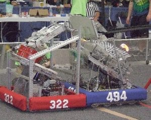 Goodrich Martian's robot 494 is blocked from maneuvering through the arena with a strong head to head push from the Flint Fire #322 robot.