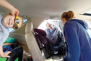 Ben, 4, of Owosso mugs for the camera while his mom gets help installing his new car seat, appropriate for his size and weight, during a safety check by Safe Kids hosted by HealthPlus.