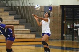 Tori Henderson (5) on serve for the Carman-Ainsworth varsity volleyball squad.