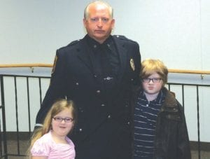 Randy Kimes shown with his grandchildren after being promoted to sergeant last year.