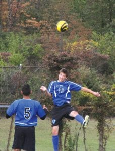 Carman-Ainsworth's Zach Smith heads the ball in front of teammate Anas Morsi.
