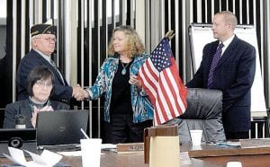 William Cool, sixth district commander for the American Legion of Michigan presents flag donations to Carman-Ainsworth school board President Patrice Hatcher and Superintendent Steve Tunnicliff.