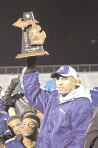 Carman-Ainsworth coach Nate Williams hoists the district championship trophy after last Friday's win over Brighton.