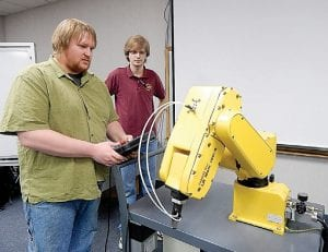 Eric Rix (left) and Alex White, third-year engineering students and members of the Baker College of Flint chapter of the American Society of Mechanical Engineers demonstrate a FANUC robot in the Robotics Lab during an Open House last week. The FANUC robot is a small-scale version of those used in automotive assembly plants.