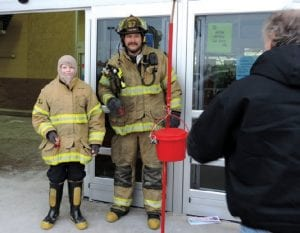 A Flint Township Firefighter with a little helper were among the township Firefighters Association members who took turns last weekend ringing the bell for Salvation Army donations during a two-day stint outside of the Walmart store on Corunna Road.