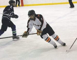 Flushing's Joe Montpas chases the puck through the neutral zone during a Jan. 25 game against Lapeer.