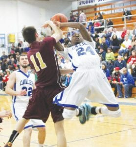Carman-Ainsworth's Ja'Quin Jones gets fouled by Davison's Andrew Miller in the district opener on Monday at Carman- Ainsworth.