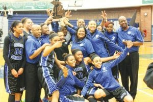The Lady Cavs celebrate the first girls' basketball regional title in school history last Thursday at Saginaw Heritage.