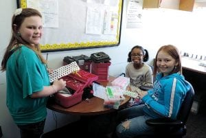 Emma Bell, Kelcee Ballard and Madison Bright, fourth-graders at Randels Elementary School, are making and selling their Rainbow Loom jewelry to help a schoolmate whose home was recently destroyed in a fire.