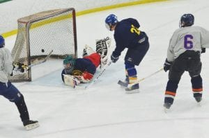 Lapeer West goalie Brad Post (#30) allows a goal to Carman-Ainsworth in the first period of last Friday's 30-and-over alumni hockey game as #6 looks on.