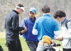 Carman-Ainsworth's Haywood Petty (second from left) adds up scores after the Genesee County Invitational.