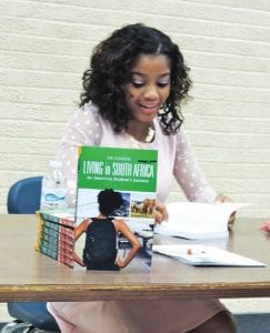 CAHS senior Rani Richardson autographs a copy of her new book at a book-signing event last week. Richardson (left) poses with her family during her book signing at the high school.