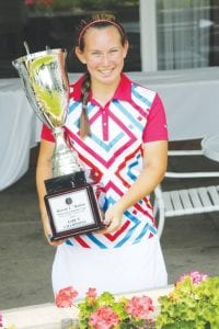 Flushing's Kerri Parks holds the Mallon Cup after winning the girls' championship Monday at Flint Golf Club.