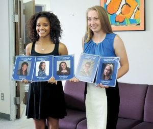 Rani Richardson and Katlyn Koegel (left to right) display their Academic Hall of Fame induction plaques along with those of their classmates who could not attend a special recognition held last week during the school board meeting.