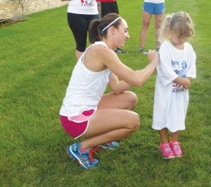Geena Gall signs the T-shirt of one of the youngest runners.
