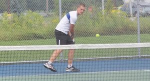 Carman-Ainsworth's Damon Haley connects on a return at the Lapeer courts back in August.
