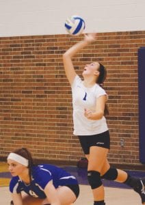 Carman-Ainsworth's Sarah Thurston goes up for a serve as teammate Korbin Brandon waits.