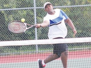 Carman-Ainsworth's Evan Walker stretches for a return at No. 3 Singles.