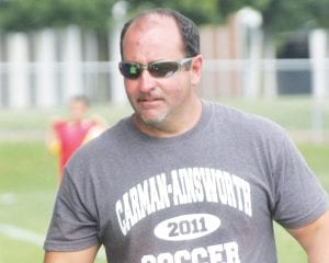 Head coach Jay Witham stands on the sidelines during a Cavaliers varsity soccer game.