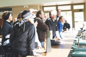 Lake Orion, Grand Blanc (center) and other top teams leaned over the table to check their scores against other teams at the Div. 1 golf regional at the Lapeer Country Club last Wednesday.