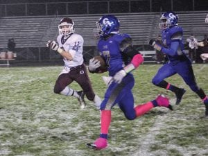 Carman-Ainsworth's Tyler Minor (7) dashes through the snow for some of his 200 yards against Okemos last Friday. Teammate Josh Jackson (4) comes up to try to block Okemos' Kyle Krumm.