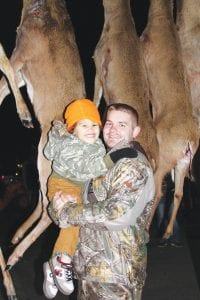 2014 Genesee County buck pole winner Daniel Phillips of Grand Blanc with his son, 4-year-old Landen.