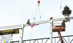 Raising an evergreen and flag to the last beam set in place is a time-honored builders tradition conducted last week by steel workers at Flint Assembly's new paint shop under construction.