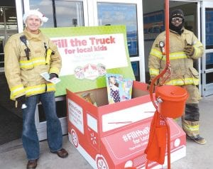 Above, firefighters collected money and toys in front of Wal-Mart. A Mitten Tree is on display at the township hall and boxes are set up to collect toys and food donations.