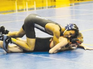 Carman-Ainsworth's Damion Wilkes works over his opponent.