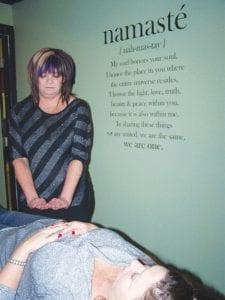 Lisa Lewis demonstrates Reiki techniques for Sherry Hansen of Swartz Creek, at Hair to Toe salon.