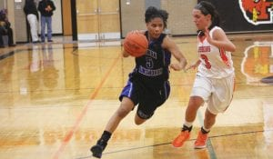 Carman-Ainsworth's Harmany Williams drives into the lane against Flushing's Kamryn Chappell in Tuesday night's game at Flushing.