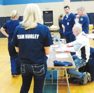 Dr. Jim Weber (seated) was among about 50 Hurley volunteers who conducted the free teen health screenings. Right, Phillip Woodbury, 11, of Swartz Creek gets an electrocardiogram to check the electrical activity of his heart during a Teen Health Check screening at CAMS last weekend.