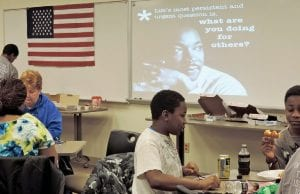 Under the watchful visage of Dr. Martin Luther King Jr., projected on a large screen, volunteers worked to make 400 paracord survival bracelets as part of Davenport University's MLK Day of Service. Above, half of the finished bracelets were boxed for shipment to military personnel serving overseas.