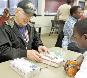 Jim Stewart, a Vietnam Veteran, helped Donnell Underwood, a sixth-grader at Randels Elementary School, as the two sat together weaving cord into survival bracelets to be donated to military personnel and first responders.